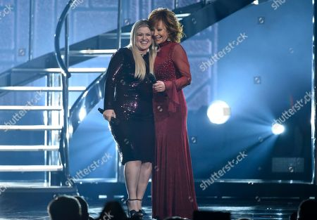 """Kelly Clarkson, Reba McEntire. Kelly Clarkson, left, and Reba McEntire hug after performing """"Does He Love You"""" at the 53rd annual Academy of Country Music Awards at the MGM Grand Garden Arena, in Las Vegas"""