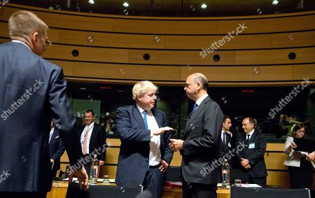 British Foreign Secretary Boris Johnson, center left, speaks with Italian Foreign Minister Angelino Alfano, right, during a meeting of EU foreign ministers at the EU Council building in Luxembourg on