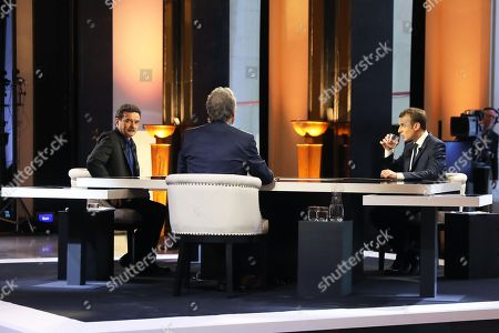 French President Emmanuel Macron poses on the TV set before an interview with RMC-BFM French journalist Jean-Jacques Bourdin and Mediapart investigative website French journalist Edwy Plenel