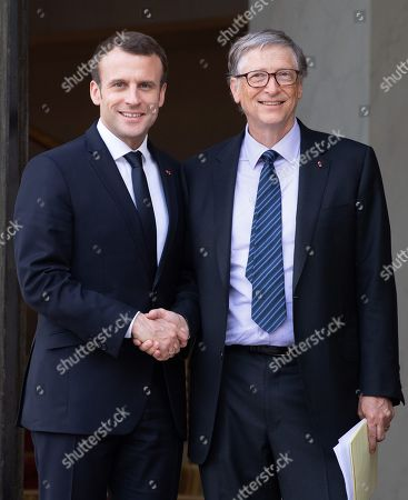 French President Emmanuel Macron (L) shakes hands with US business magnate Bill Gates, Microsoft co-founder and co-chair of the Bill & Melinda Gates Foundation, at the Elysee Palace
