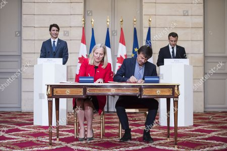 Stock Photo of French President Emmanuel Macron (R) and Canadian Prime Minister Justin Trudeau (L) look on as French Minister for the Ecological and Inclusive Transition Nicolas Hulot (2nd R) and Canadian Minister of Environment and Climate Change Catherine McKenna (2nd L) sign an ecology agreement at the Elysee Palace