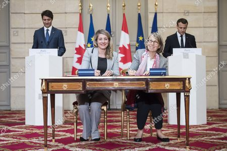 French President Emmanuel Macron (R) and Canadian Prime Minister Justin Trudeau (L) look as French Culture Minister Francoise Nyssen (2nd R) and Canadian Heritage Minister Melanie Joly (2nd L) sign an agreement at the Elysee Palace