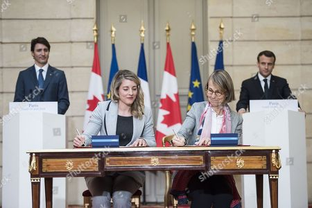 Stock Photo of French President Emmanuel Macron (R) and Canadian Prime Minister Justin Trudeau (L) look as French Culture Minister Francoise Nyssen (2nd R) and Canadian Heritage Minister Melanie Joly (2nd L) sign an agreement at the Elysee Palace