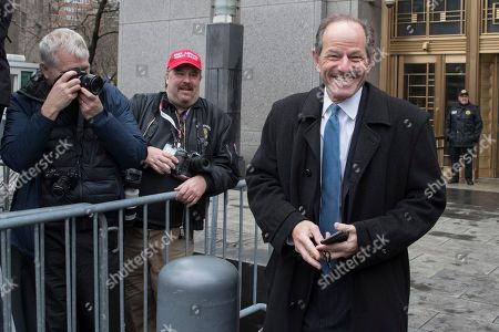 Former New York Gov. Eliot Spitzer, right, walks past photographers assembled outside federal court for a hearing for Michael Cohen, President Donald Trump's personal attorney, in New York. Spitzer was in court on an unrelated matter