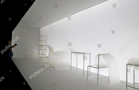 Stock Photo of A visitor watches the installation of the Nendo studios of designer Oki Sato during the first day of the Design Week, in Milan, Italy, . The Milan Design week is taking place in various locations across Milan from April 17 through 22, 2018