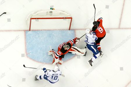 New Jersey Devils goaltender Cory Schneider (35) protects his net with the help of left wing Taylor Hall (9) as Tampa Bay Lightning center J.T. Miller (10) and defenseman Ryan McDonagh (27) attack during the third period of Game 3 of an NHL first-round hockey playoff series, in Newark, N.J. The Devils won 5-2