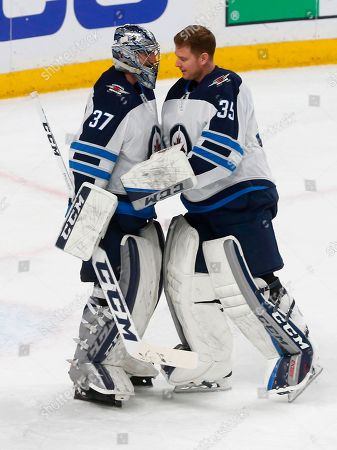 Stock Image of Connor Hellebuyck, Steve Mason. Winnipeg Jets goalie Connor Hellebuyck, left, is congratulated by goalie Steve Mason after Hellebuyck shut out the Minnesota Wild 2-0 in Game 4 of an NHL hockey first-round playoff series, in St. Paul, Minn