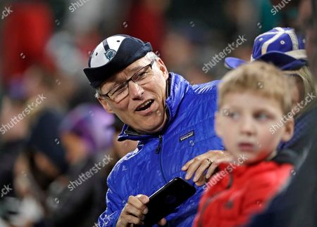 """Washington Gov. Jay Inslee wears his Seattle Mariners ball cap inside-out, """"rally"""" style, during the ninth inning of the Mariners' baseball game against the Houston Astros, in Seattle. The Astros won 4-1"""
