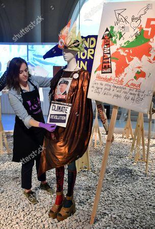 Vivian Westwood dress, sleeves and stockings, 2012. Vivian Westwood 'Ecotricity crown', 2017. Vivian Westwood 'Climate Revolution' shoes, 2013. Vivian Westwood 'Save the Arctic' T-shirt, 2015. Vivian Westwood Archive 'Uninhabitable land' placard, 2016.
