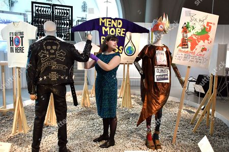 Stock Picture of (L) Katherine Hamnett 'Clean Up or Die' man's ensemble, 1989. (Background middle) Bridget Harvey 'Mend More' Jumper, 2015. (R) Vivian Westwood dress, sleeves and stockings, 2012. Vivian Westwood 'Ecotricity crown', 2017. Vivian Westwood 'Climate Revolution' shoes, 2013. Vivian Westwood 'Save the Arctic' T-shirt, 2015. Vivian Westwood Archive 'Uninhabitable land' placard, 2016.