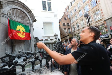 Belgian artist Stromae makes a surprise visit at the statue of Manneken Pis during the inauguration of his new costume
