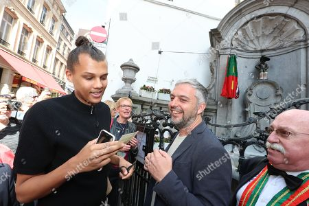 Stock Image of Belgian artist Stromae makes a surprise visit at the statue of Manneken Pis during the inauguration of his new costume
