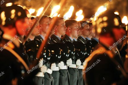 Soldiers take their helmets off during a Grand Tattoo military ceremony in honor of Chief of Staff of the Bundeswehr, General Volker Wieker, in the Ministry of Defence, in Berlin, Germany, 18 April 2018. General Wieker is being awarded the honor of a Grand Tattoo after 44 years of service in the German armed forces, eight of them as Chief of Staff. The Grand Tattoo is the highest military ceremony the German armed forces (Bundeswehr) award and is executed in the evening with a military formation carrying torches and a band playing various marches.