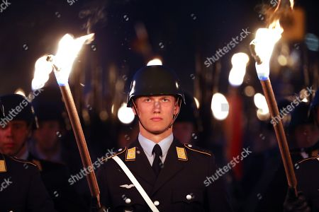 A soldier parades with a torch during a Grand Tattoo military ceremony in honor of Chief of Staff of the Bundeswehr, General Volker Wieker, in the Ministry of Defence, in Berlin, Germany, 18 April 2018. General Wieker is being awarded the honor of a Grand Tattoo after 44 years of service in the German armed forces, eight of them as Chief of Staff. The Grand Tattoo is the highest military ceremony the German armed forces (Bundeswehr) award and is executed in the evening with a military formation carrying torches and a band playing various marches.