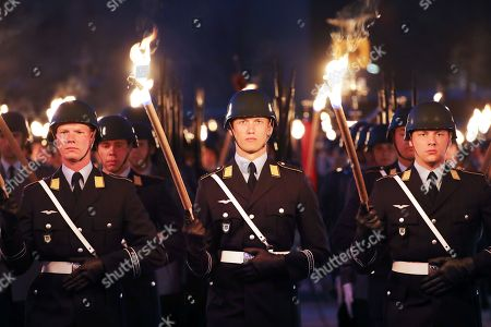 Soldiers parade with torches during a Grand Tattoo military ceremony in honor of Chief of Staff of the Bundeswehr, General Volker Wieker, in the Ministry of Defence, in Berlin, Germany, 18 April 2018. General Wieker is being awarded the honor of a Grand Tattoo after 44 years of service in the German armed forces, eight of them as Chief of Staff. The Grand Tattoo is the highest military ceremony the German armed forces (Bundeswehr) award and is executed in the evening with a military formation carrying torches and a band playing various marches.