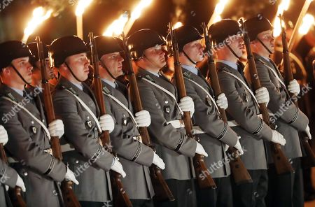 Soldiers hold their rifles during a Grand Tattoo military ceremony in honor of Chief of Staff of the Bundeswehr, General Volker Wieker, in the Ministry of Defence, in Berlin, Germany, 18 April 2018. General Wieker is being awarded the honor of a Grand Tattoo after 44 years of service in the German armed forces, eight of them as Chief of Staff. The Grand Tattoo is the highest military ceremony the German armed forces (Bundeswehr) award and is executed in the evening with a military formation carrying torches and a band playing various marches.