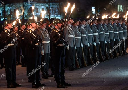 Stock Photo of Soldiers hold torches during a Grand Tattoo military ceremony in honor of Chief of Staff of the Bundeswehr, General Volker Wieker, in the Ministry of Defence, in Berlin, Germany, 18 April 2018. General Wieker is being awarded the honor of a Grand Tattoo after 44 years of service in the German armed forces, eight of them as Chief of Staff. The Grand Tattoo is the highest military ceremony the German armed forces (Bundeswehr) award and is executed in the evening with a military formation carrying torches and a band playing various marches.