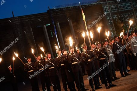 Soldiers hold torches during a Grand Tattoo military ceremony in honor of Chief of Staff of the Bundeswehr, General Volker Wieker, in the Ministry of Defence, in Berlin, Germany, 18 April 2018. General Wieker is being awarded the honor of a Grand Tattoo after 44 years of service in the German armed forces, eight of them as Chief of Staff. The Grand Tattoo is the highest military ceremony the German armed forces (Bundeswehr) award and is executed in the evening with a military formation carrying torches and a band playing various marches.