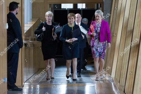 Scottish Parliament First Minister's Questions - Shona Robison, Cabinet Secretary for Health, Wellbeing and Sport, Nicola Sturgeon, First Minister of Scotland and Leader of the Scottish National Party (SNP), and Roseanna Cunningham, Cabinet Secretary for Environment, Climate Change and Land Reform, make their way to the Debating Chamber.