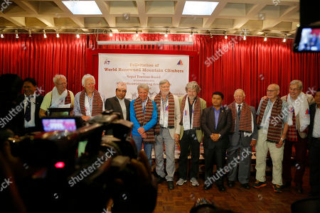 Italian mountaineer Reinhold Messner, fifth right, and Austrian Peter Habeler, fifth left, attend a felicitation program along with other mountaineers in Kathmandu, Nepal, . Nepal's government on Thursday honored the two climbers who were the first to scale Mount Everest without supplementary oxygen 40 years ago. Messner and Habeler reached the summit without use of supplementary oxygen, while others on their team used bottled oxygen