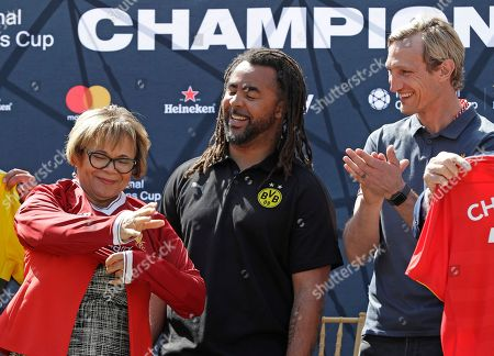 Vi Lyles, Sami Hyypia, Patrick Owomoyela. Charlotte, N.C. mayor Vi Lyles, left, tries on a jersey from former Liverpool soccer star Sami Hyypia, right, as former Borussia Dortmund soccer star Patrick Owomoyela, center, looks on during a news conference in Charlotte, N.C., . Liverpool F.C. will play Borussia Dortmund on July 22, 2018, in Charlotte, N.C. as part of the International Champions Cup