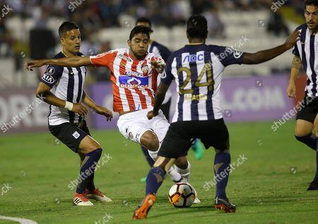 Luis Ruiz, Miguel Araujo. Luis Ruiz of Colombia's Junior, center, fights for the ball with Miguel Araujo (24) of Peru's Alianza Lima during a Copa Libertadores soccer match in Lima, Peru
