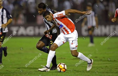 Luis Ruiz, Miguel Araujo. Luis Ruiz of Colombia's Junior, behind, fights for the ball with Miguel Araujo of Peru's Alianza Lima during a Copa Libertadores soccer match in Lima, Peru