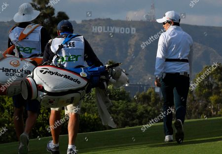 Eun-Hee Ji, of South Korea, walks up the ninth fairway with the her caddie, left, and the caddie of Mirim Lee, of South Korea, during the first round of the HUGEL-JTBC LA Open golf tournament at Wilshire Country Club, in Los Angeles