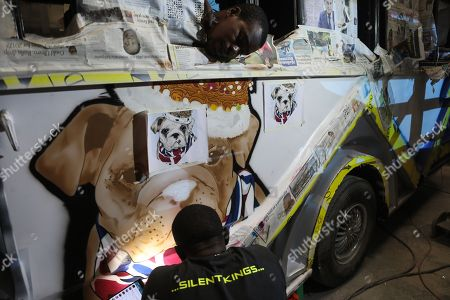 A graffiti designer (bottom) paints a matatu with a graffiti portrait of a pit bull dog, before being fitted with lights, screens and sound system at the Choda fabricators garage in Nairobi, Kenya, 05 April 2018. Kenya is known to have public service vehicles especially the mini buses decorated with graffiti, interior design, loud music and flat screens that gives it the atmosphere of a disco as a way of attracting customers.