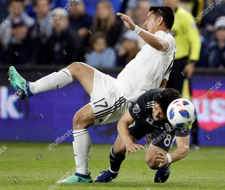 Roger Espinoza, Felipe Martins. Sporting Kansas City midfielder Roger Espinoza (17) and Vancouver Whitecaps midfielder Felipe Martins (8) battle for the ball during the first half of an MLS soccer match in Kansas City, Kan