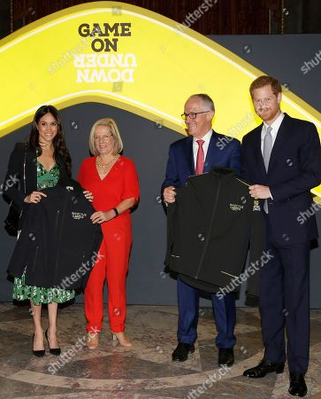 Britain's Prince Harry and Meghan Markle receive Invictus Games jackets from Malcolm Turnbull, Prime Minister of Australia and his wife Lucy Turnbull, as they attend a reception at Australia House in London, to celebrate the forthcoming Invictus Games Sydney 2018