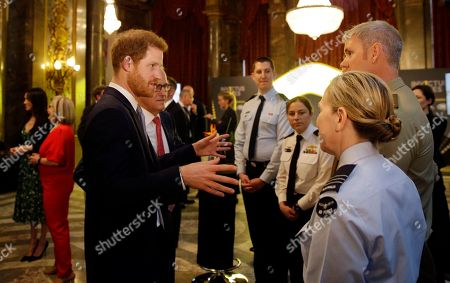 Britain's Prince Harry talks to members of the Australian Defence Force as he and Meghan Markle attend a reception hosted by Malcolm Turnbull, Prime Minister of Australia and his wife Lucy Turnbull at Australia House in London, to celebrate the forthcoming Invictus Games Sydney 2018
