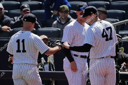 New York Yankees pitcher Jordan Montgomery (47) greets left fielder Brett Gardner (11) after Gardner made a catch deep in the left field corner to end the top of the first inning against the Toronto Blue Jays in a baseball game, in New York