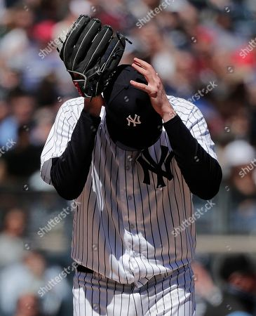 New York Yankees pitcher Jordan Montgomery adjusts his cap during the third inning of a baseball game against the Toronto Blue Jays, in New York