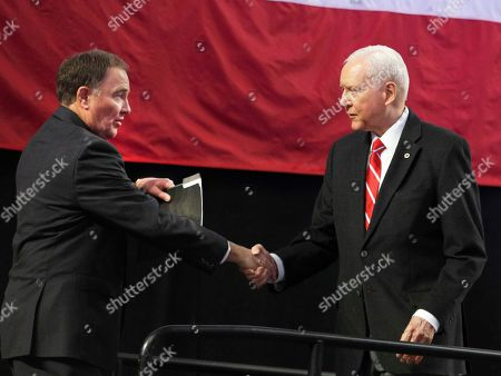Utah Governor Gary Herbert, left, greets Utah U.S. Senator Orin Hatch, as he prepares to speak at the Utah Republican 2018 nominating convention, in West Valley City, Utah. Mitt Romney is facing nearly a dozen Republican contenders in Utah on Saturday as he works to secure the state GOP nomination for a Senate seat without a primary
