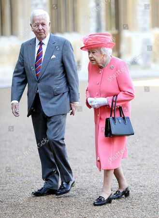 Britain's Queen Elizabeth II walks with John Spurling, Chairman of London Marathon Events, after pressing a button to start the London Marathon from Windsor Castle, Windsor, England, which was relayed to big screens at the start of the Marathon setting off 40,000 runners