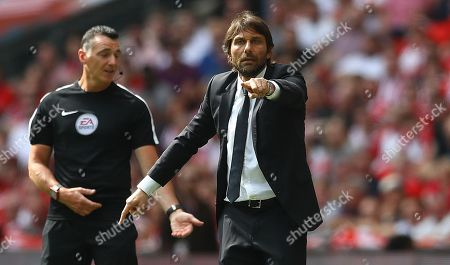 Fourth official Neil Swarbrick gestures to Chelsea manager Antonio Conte