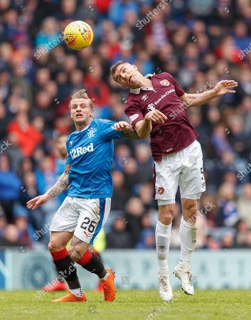 Aaron Hughes of Heart of Midlothian heads away from Jason Cummings of Rangers