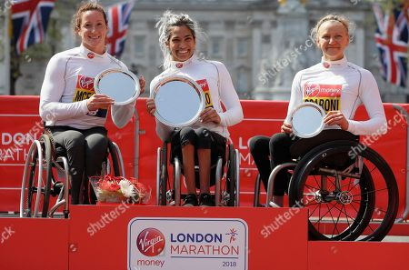 Madison de Rozario of Australia placed first, centre, Tatyana McFadden of USA placed second, left, and Susannah Scaroni of USA placed third, during presentations for the Women's Wheelchair race in the London Marathon in London