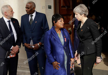 Britain's Prime Minister Theresa May, right, talks with and Doreen Lawrence, the mother of Stephen Lawrence, as opposition Labour party leader Jeremy Corbyn, left, talks with Neville Lawrence, the father of Stephen Lawrence, as they leave a Memorial Service to commemorate the 25th anniversary of the murder of black teenager Stephen Lawrence at St Martin-in-the-Fields church in London