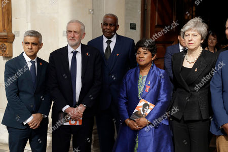 Doreen, fourth left, and Neville Lawrence, third left, the mother and father of Stephen Lawrence, pose for a group photograph with Britain's Prime Minister Theresa May, right, opposition Labour party leader Jeremy Corbyn, second left, and London mayor Sadiq Khan, left, as they leave a Memorial Service to commemorate the 25th anniversary of the murder of black teenager Stephen Lawrence at St Martin-in-the-Fields church in London