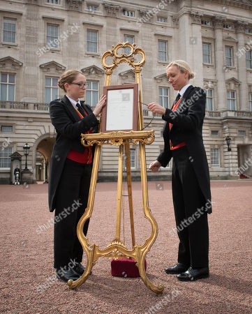 Senior footman Olivia Smith (left) and footman Heather McDonald place a notice on an easel in the forecourt of Buckingham Palace in London to formally announce the birth of a baby boy to the Duke and Duchess of Cambridge at St Mary's Hospital.