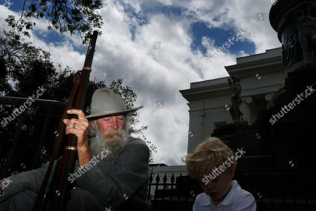 Dan Williams, 68, of Asheville, Ala., sits with a young boy and rests on a set of stairs at the Alabama state Capitol to celebrate Confederate Memorial Day, in Montgomery, Ala