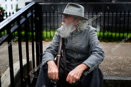 Dan Williams, 68, of Asheville, Ala., sits and rests on a set of stairs at the Alabama state Capitol to celebrate Confederate Memorial Day, in Montgomery, Ala