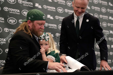 New York Jets center Nick Mangold, left, holds his 3-year-old daughter, Eloise, while signing a contract as team owner Christopher Johnson looks on during a news conference making his official retirement from NFL football, in Florham Park, N.J. Mangold announced his retirement a week earlier in a post on Twitter. He was selected to seven Pro Bowls and was twice a first-team All-Pro during his 11-year career