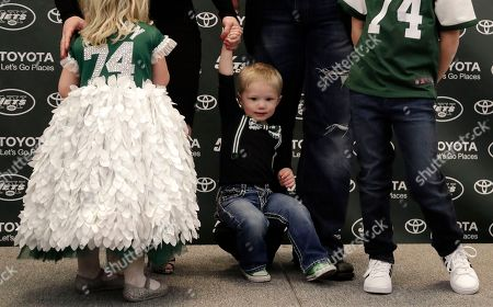 Thomas Mangold, center, son of New York Jets center Nick Mangold, rests on his father's foot during a family portrait at a news conference making Nick Mangold's official retirement from NFL football, in Florham Park, N.J. Mangold announced his retirement a week earlier in a post on Twitter. He was selected to seven Pro Bowls and was twice a first-team All-Pro during his 11-year career