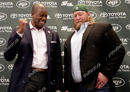 Former New York Jets offensive tackle D'Brickashaw Ferguson, left, pretends to cry as he talks to center Nick Mangold following a news conference making Mangold's official retirement from NFL football, in Florham Park, N.J. Mangold announced his retirement a week earlier in a post on Twitter. He was selected to seven Pro Bowls and was twice a first-team All-Pro during his 11-year career