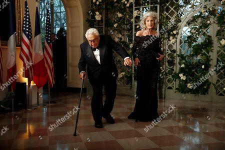 Henry Kissinger, Nancy Kissinge. Former Secretary of State Henry Kissinger stumbles as his wife Nancy Kissinger stands, as they arrive for a State Dinner with French President Emmanuel Macron and President Donald Trump at the White House, in Washington