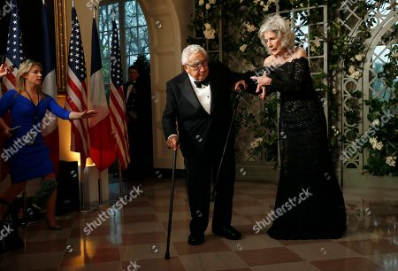 Henry Kissinger, Nancy Kissinger, Kelly Love. White House staffer Kelly Love, left, reaches out as former Secretary of State Henry Kissinger stumbles as his wife Nancy Kissinger holds him as they arrive for a State Dinner with French President Emmanuel Macron and President Donald Trump at the White House, in Washington