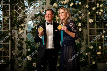 Stock Picture of John Shuster, Meghan Duggan. Olympians John Shuster and Meghan Duggan hold up their Olympic gold medals as they arrive for a State Dinner with French President Emmanuel Macron and President Donald Trump at the White House, in Washington